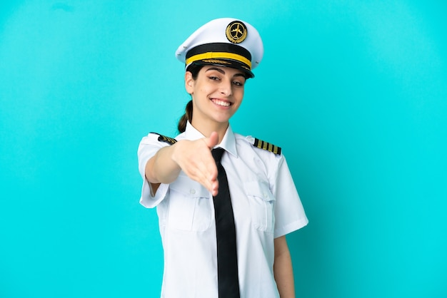Pilota di aereo donna caucasica isolata su sfondo blu che stringe la mano per chiudere un buon affare