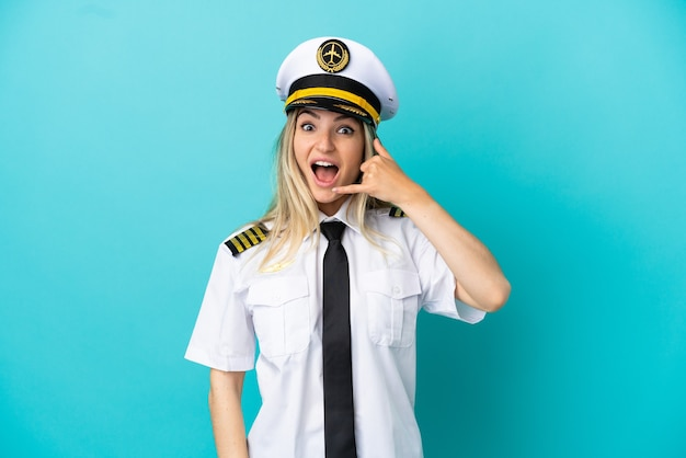 Pilota dell'aeroplano sopra fondo blu isolato che fa gesto del telefono. richiamami segno