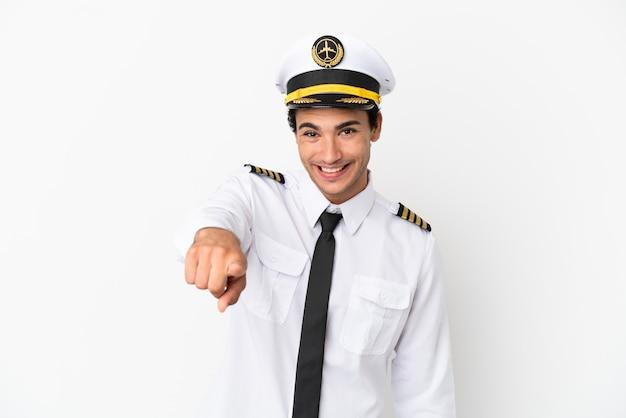Il pilota dell'aeroplano su uno sfondo bianco isolato ti punta il dito contro con un'espressione sicura