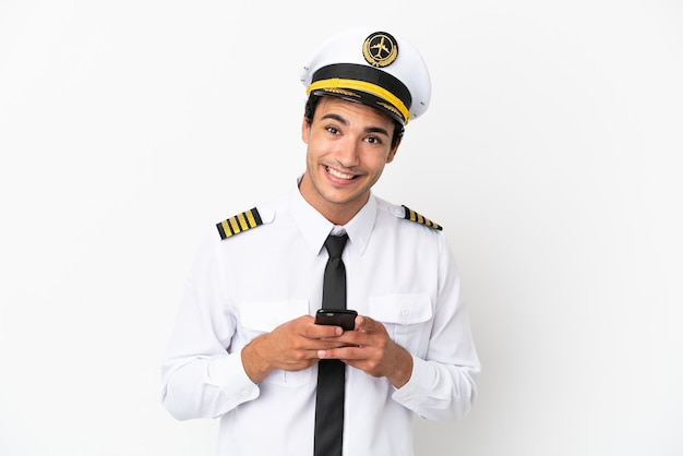 Pilota di aeroplano su sfondo bianco isolato inviando un messaggio con il cellulare
