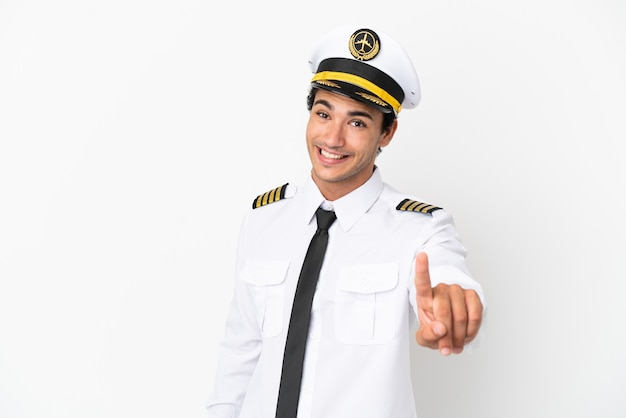 Pilota di aeroplano su sfondo bianco isolato che mostra e solleva un dito