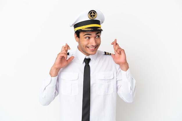 Pilota di aeroplano su sfondo bianco isolato con le dita incrociate