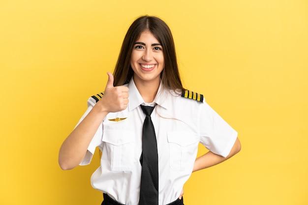 Pilota di aeroplano isolato su sfondo giallo che dà un gesto di pollice in alto
