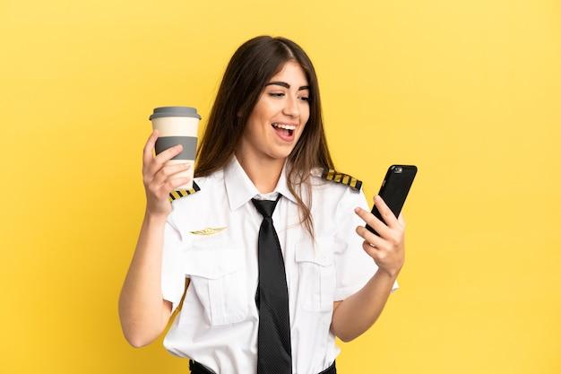 Pilota di aeroplano isolato su sfondo giallo che tiene il caffè da portare via e un cellulare