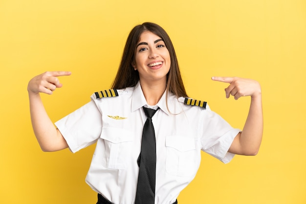 Pilota di aeroplano isolato su sfondo giallo orgoglioso e soddisfatto di sé