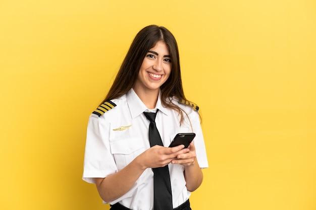 Pilota di aeroplano isolato su sfondo giallo che invia un messaggio con il cellulare