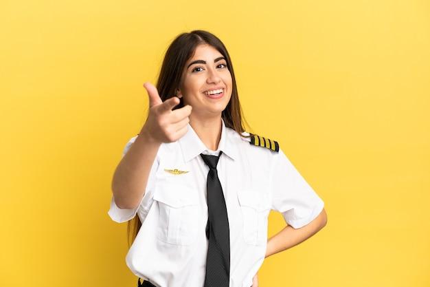 Pilota di aeroplano isolato su sfondo giallo con il pollice in alto perché è successo qualcosa di buono