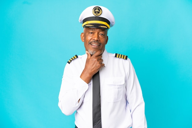 Uomo anziano pilota di aeroplano isolato su sfondo blu felice e sorridente