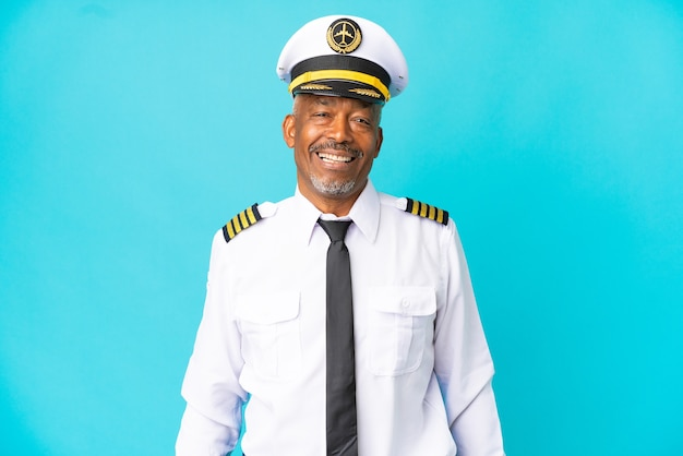 Uomo anziano pilota di aeroplano isolato su sfondo blu ridendo