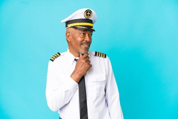 Pilota di aeroplano uomo anziano isolato su sfondo blu guardando di lato e sorridente