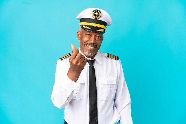 Uomo anziano pilota di aeroplano isolato su sfondo blu che fa gesto di denaro
