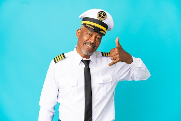 Uomo anziano pilota di aeroplano isolato su sfondo blu che fa gesto di telefono. richiamami segno