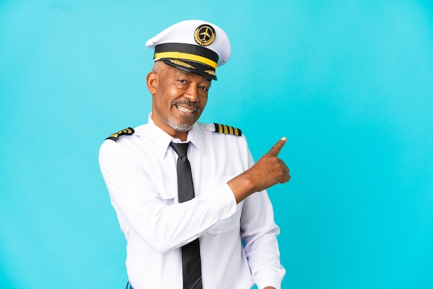 Pilota di aeroplano uomo anziano isolato su sfondo blu che punta indietro