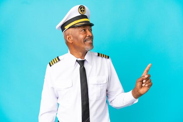 Uomo anziano pilota di aeroplano isolato su sfondo blu che indica una grande idea
