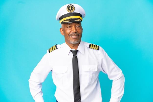 Pilota di aeroplano uomo anziano isolato su sfondo blu in posa con le braccia all'anca e sorridente