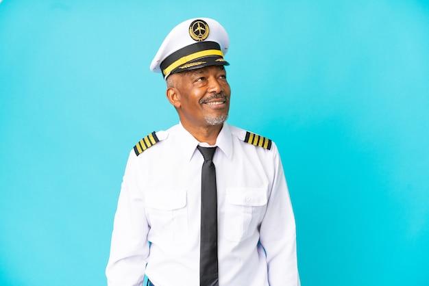 Uomo anziano pilota di aeroplano isolato su sfondo blu pensando a un'idea mentre guarda in alto