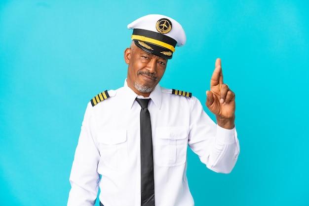 Uomo anziano pilota di aeroplano isolato su sfondo blu con le dita incrociate e augurando il meglio