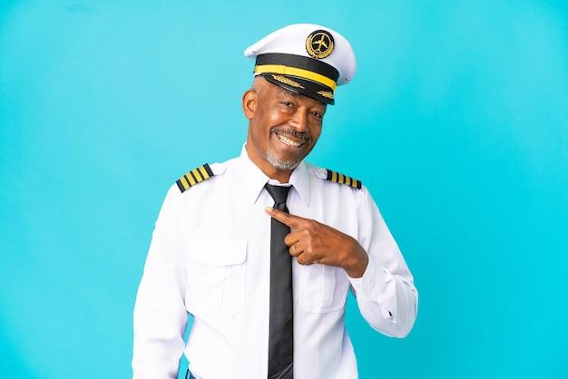 Uomo anziano pilota di aeroplano isolato su sfondo blu con espressione facciale a sorpresa