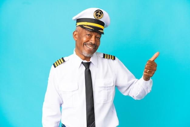 Uomo anziano pilota di aeroplano isolato su sfondo blu con il pollice in alto perché è successo qualcosa di buono