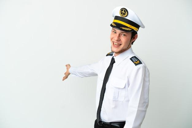 Pilota russo dell'aeroplano isolato su fondo bianco che estende le mani al lato per invitare a venire