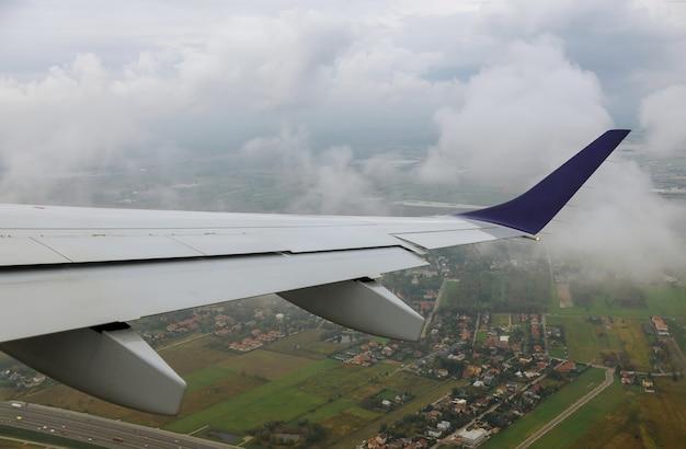 Aeroplano nel cielo sopra i campi verdi l'ala è visibile attraverso il trasporto aereo della finestra.