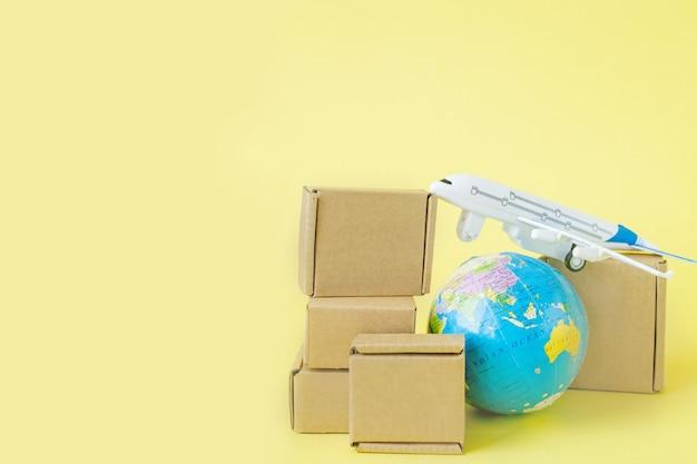 Aeroplano e pila di scatole di cartone. concetto di carico aereo e pacchi, posta aerea. consegna rapida di merci e prodotti.