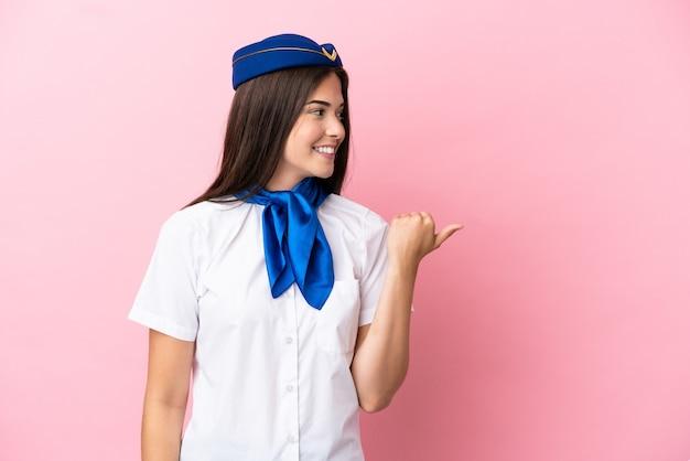 Hostess dell'aeroplano donna brasiliana isolata su sfondo rosa che punta al lato per presentare un prodotto