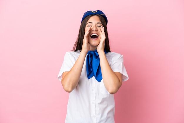 Hostess di aeroplano donna brasiliana isolata su sfondo rosa gridando e annunciando qualcosa