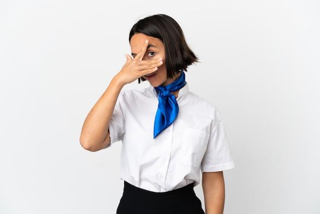 Hostess di aeroplano su sfondo isolato che copre gli occhi con le mani e sorride
