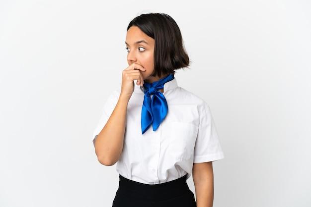 Hostess dell'aeroplano su sfondo isolato che fa un gesto a sorpresa mentre guarda di lato