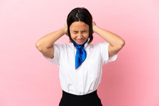 Hostess di aeroplano su sfondo isolato frustrato e che copre le orecchie