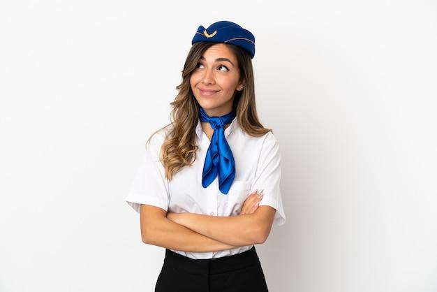 Hostess di aeroplano su sfondo bianco isolato guardando in alto mentre sorride