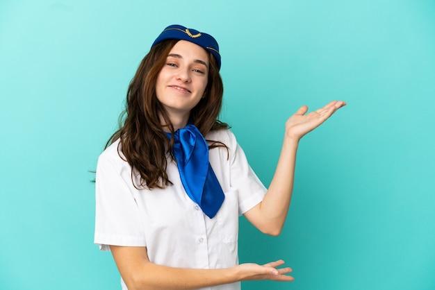 Donna hostess aeroplano isolata su sfondo blu che estende le mani di lato per invitare a venire