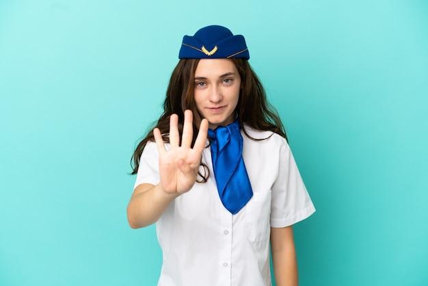 Donna hostess aereo isolata su sfondo blu felice e contando quattro con le dita