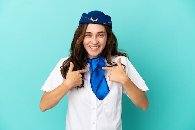 Donna hostess aeroplano isolata su sfondo blu con espressione facciale a sorpresa