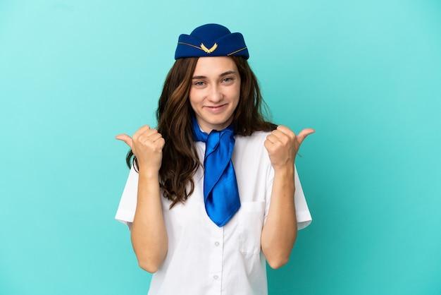 Donna hostess aeroplano isolata su sfondo blu con il pollice in alto gesto e sorridente