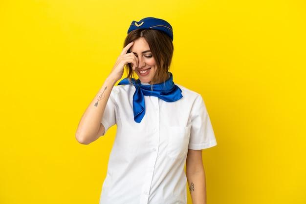 Donna hostess aeroplano isolata su sfondo giallo ridendo