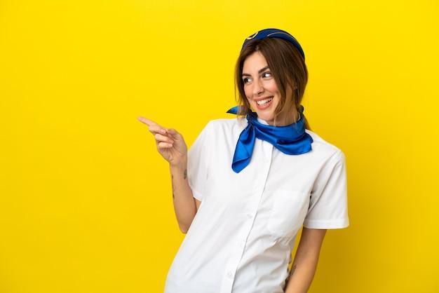 Donna hostess aeroplano isolata su sfondo giallo che punta il dito sul lato e presenta un prodotto