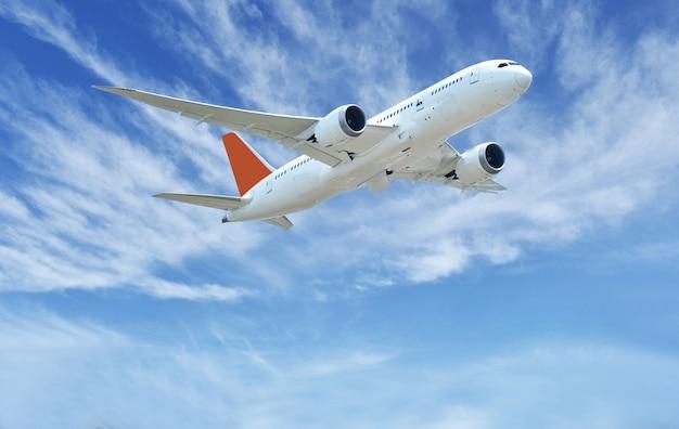 L'aeroplano decolla sui precedenti delle nuvole e del cielo blu