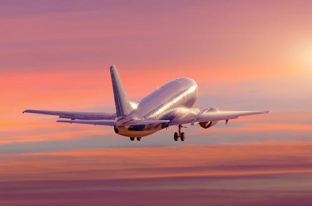 L'aereo decolla con tempo umido e umido, l'acqua scorre lungo la fusoliera quando si sale al tramonto delle nuvole rosa e viola.
