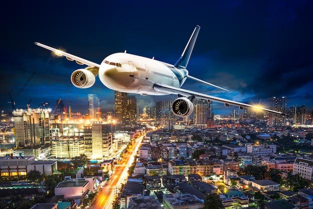 Aereo per il trasporto che sorvola il paesaggio urbano della scena notturna