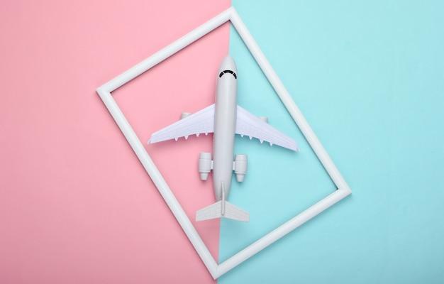Aeroplano in una cornice bianca sulla superficie pastello blu rosa