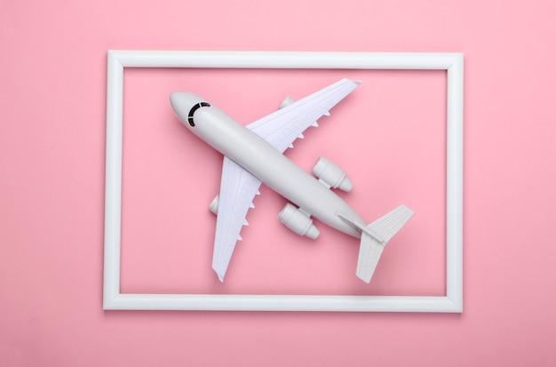 Aeroplano in una cornice bianca sulla superficie rosa
