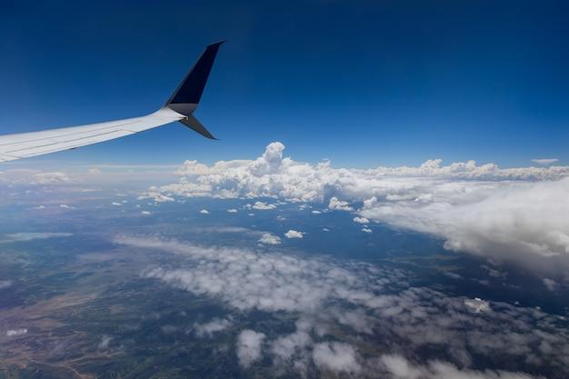Vista dell'ala dell'aeroplano fuori dalla finestra sul cielo nuvoloso sullo sfondo della terra