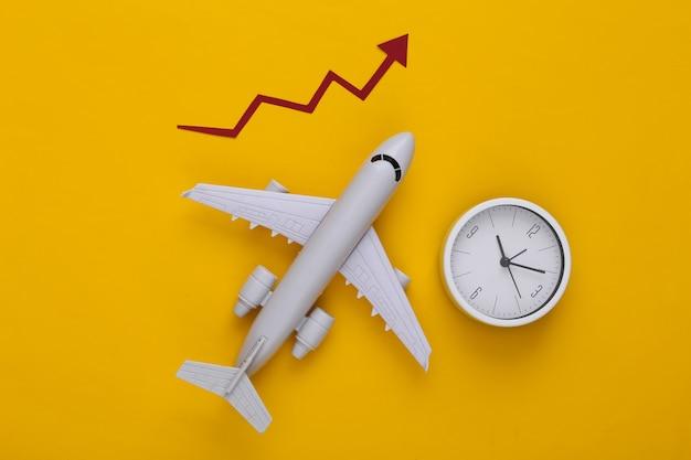 Aeroplano con freccia di crescita e orologio su un giallo Foto Premium