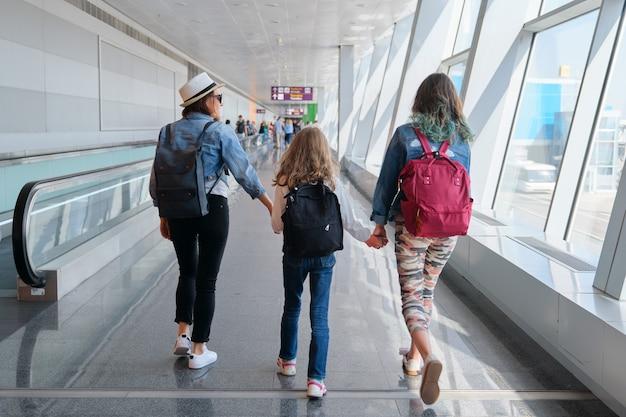 Terminal dell'aeroporto all'interno, persone che camminano passeggeri con bagagli. madre di famiglia e figlie con zaini che tengono le mani insieme