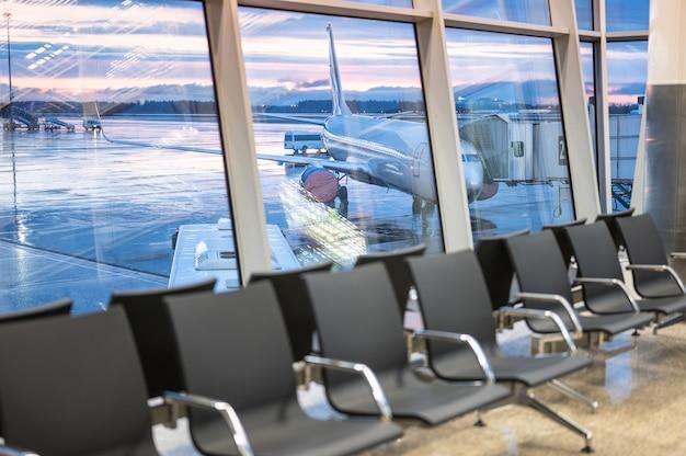 Area di attesa dell'aeroporto. aereo e cielo drammatico dietro le finestre. sedie vuote in una sala d'attesa in aeroporto