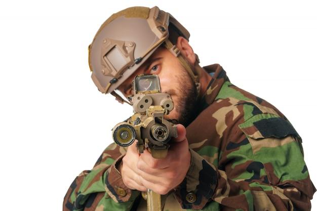 Giocatore di airsoft che mira con il suo fucile isolato su bianco