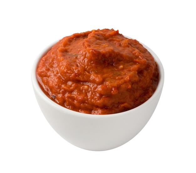 Crema spalmabile di verdure all'arancia ajvar o pindjur a base di peperoni, melanzane e olio. salsa marinara, salsa, chutney o lutenica in una ciotola bianca isolata