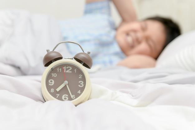 Sveglia sul letto con il ragazzo che copre le orecchie